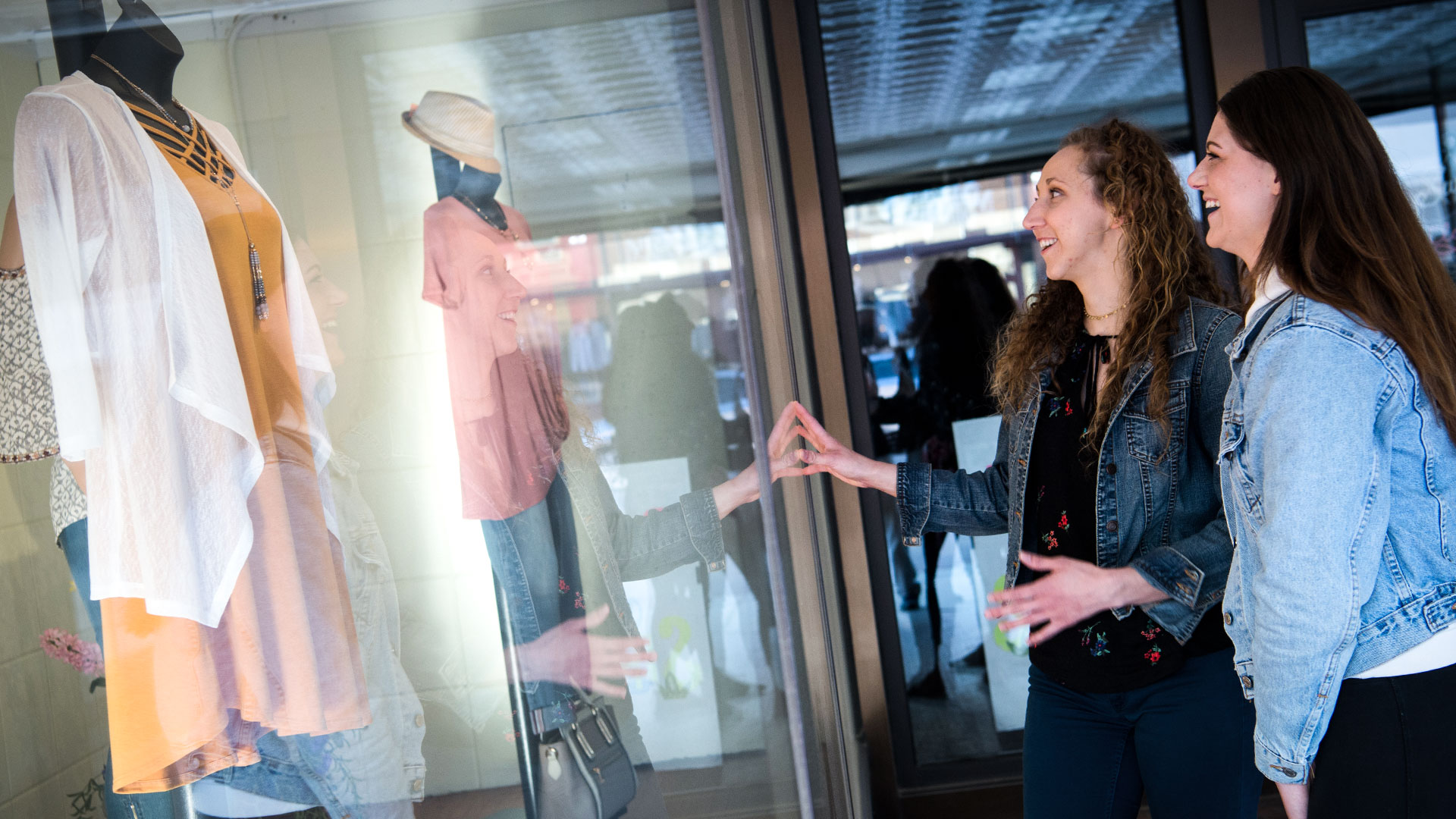 WSC students look at fashion merchandising in store window