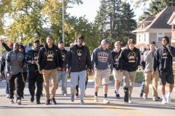 Wayne State football players walk in the Homecoming Parade on Main Street.