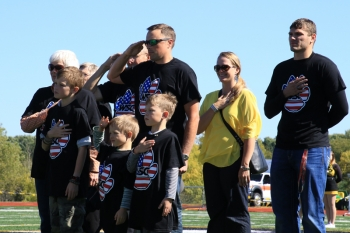 Military alumni and their families were honored during the national anthem at the football field.